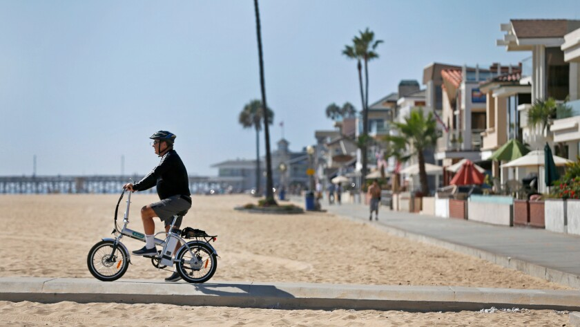 Ken Montgomery of Irvine shows off his e-bike just off the sand in Newport Beach.