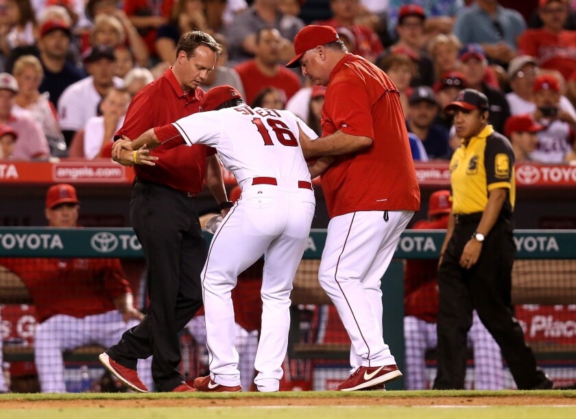 Angels Manager Mike Scioscia, right, and trainer Adam Nevala tend to pitcher Huston Street during the ninth inning against Seattle on Saturday night.