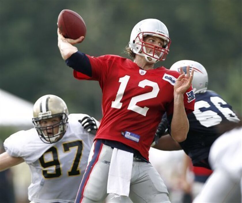New England Patriots quarterback Tom Brady throws under pressure from New Orleans Saints defensive end Jeff Charleston (97) during a joint football practice in Foxborough, Mass. Tuesday, Aug. 10, 2010. (AP Photo/Winslow Townson)