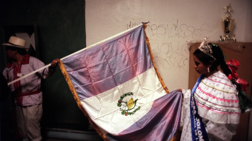 Ana Lopez looks at the Guatemalan flag before participating in a Maya ceremony in 1998 in Santa Eulalia in Guatemala. The festival was attended by Kanjobal indigenous people.