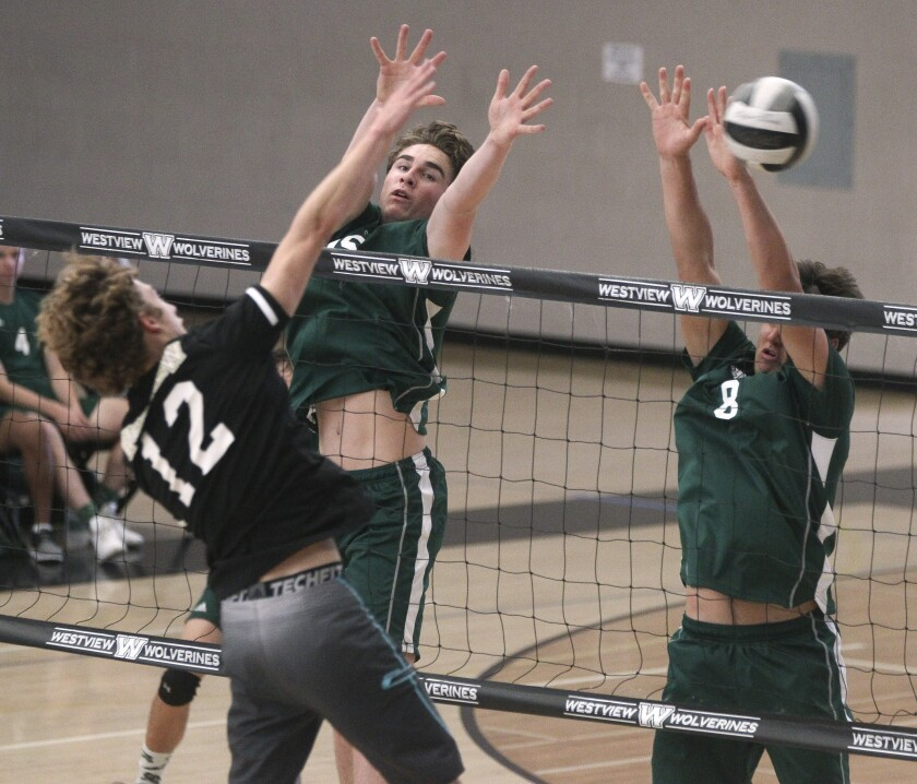 Westview's Slater Bird — who had 18 kills, three blocks and three aces — spikes the ball as Poway's Tanner Swindall (center) and Jeff Lubisich attempt to block.