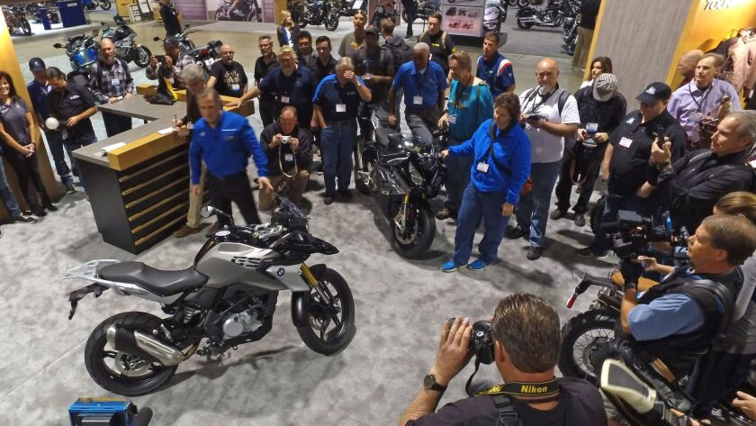 Motorcycle enthusiasts watch as BMW unveiled new product at the 2016 Progressive International Motorcycle Show in Long Beach. This year's event runs Friday through Sunday.