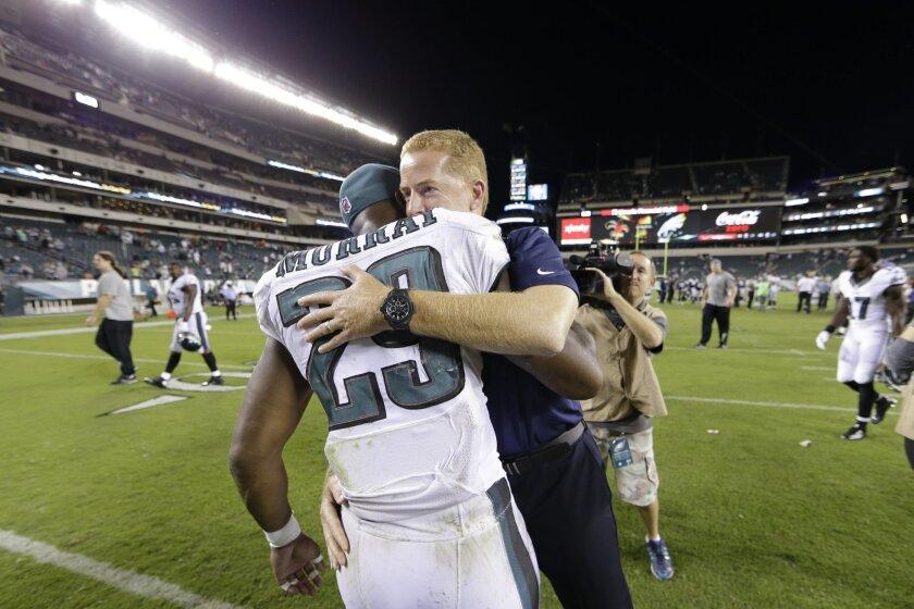 Philadelphia Eagles' DeMarco Murray, left, and Dallas Cowboys head coach Jason Garrett embrace after an NFL football game, Sunday, Sept. 20, 2015, in Philadelphia. Dallas won 20-10. (AP Photo/Matt Rourke)