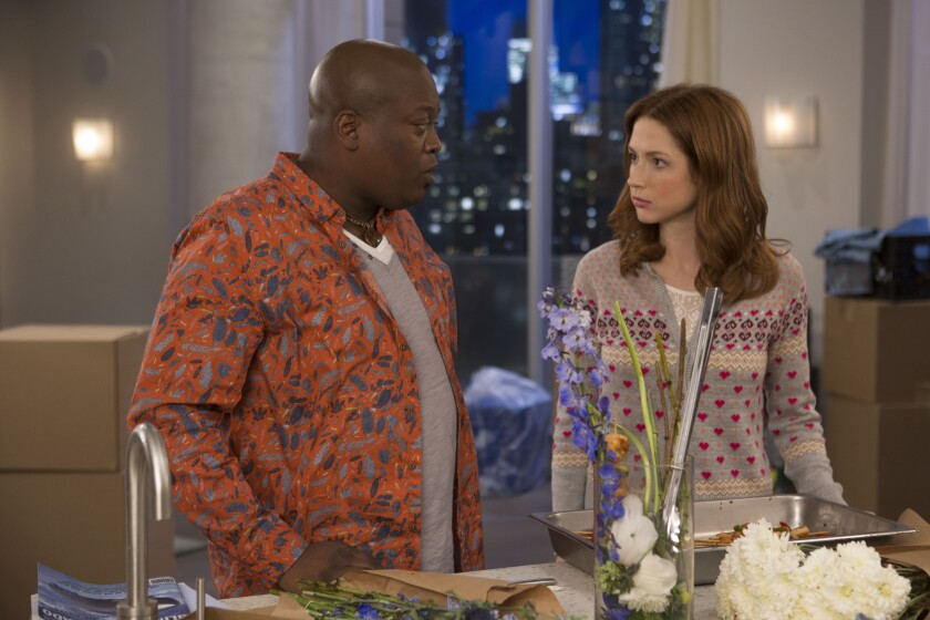 Tituss Burgess, left, and Ellie Kemper stand in front of a kitchen sink with flowers in vases.