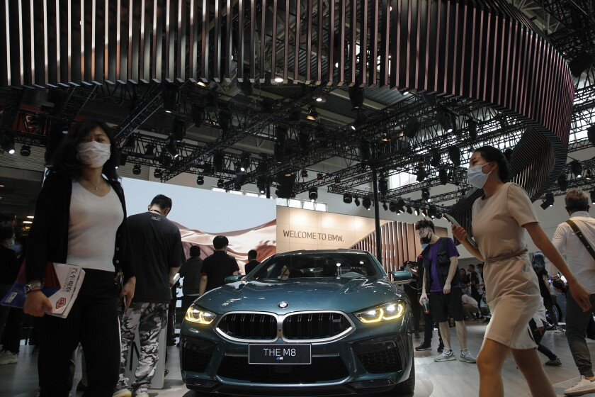 FILE - In this Sept. 27, 2020 file photo, visitors gather near a BMW M8 model on display at the Auto China 2020 show in Beijing, China. Booming sales in China helped propel German luxury carmaker BMW to stronger profits in the first three months of the year even as its home market Germany trailed the ongoing recovery in global car markets from the worst of the pandemic shutdowns. (AP Photo/Andy Wong, File)