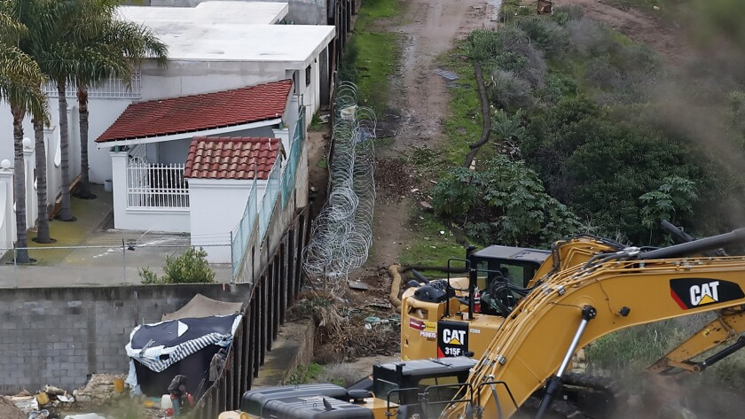 Structures in Tijuana, Mexico, left of the older section of the border wall, as machinery sits ready to continue to replace the wall with new sections, in San Diego. Border Patrol officials say some Mexican homes and structures encroach on U.S. soil posing a dilemma for authorities when replacing the wall.