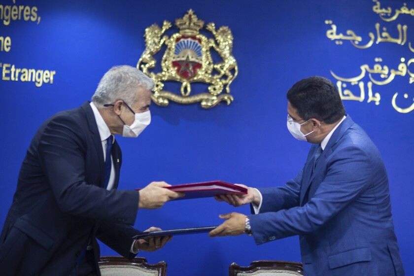 Moroccan Foreign Minister Nasser Bourita, right, and Israeli Foreign Minister Yair Lapid, left, exchange signed cooperation agreements between the two countries, in Rabat, Morocco, Wednesday, Aug. 11, 2021. The Israeli Foreign Minister Yair Lapid is on an official visit to Morocco. (AP Photo/Mosa'ab Elshamy)