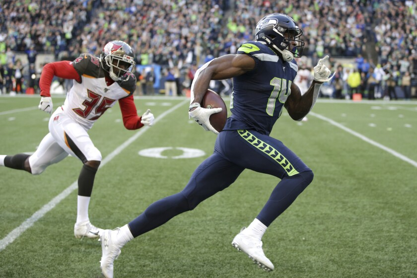 Seattle Seahawks receiver DK Metcalf (right) is entered in the 100 meters at a track meet Sunday.