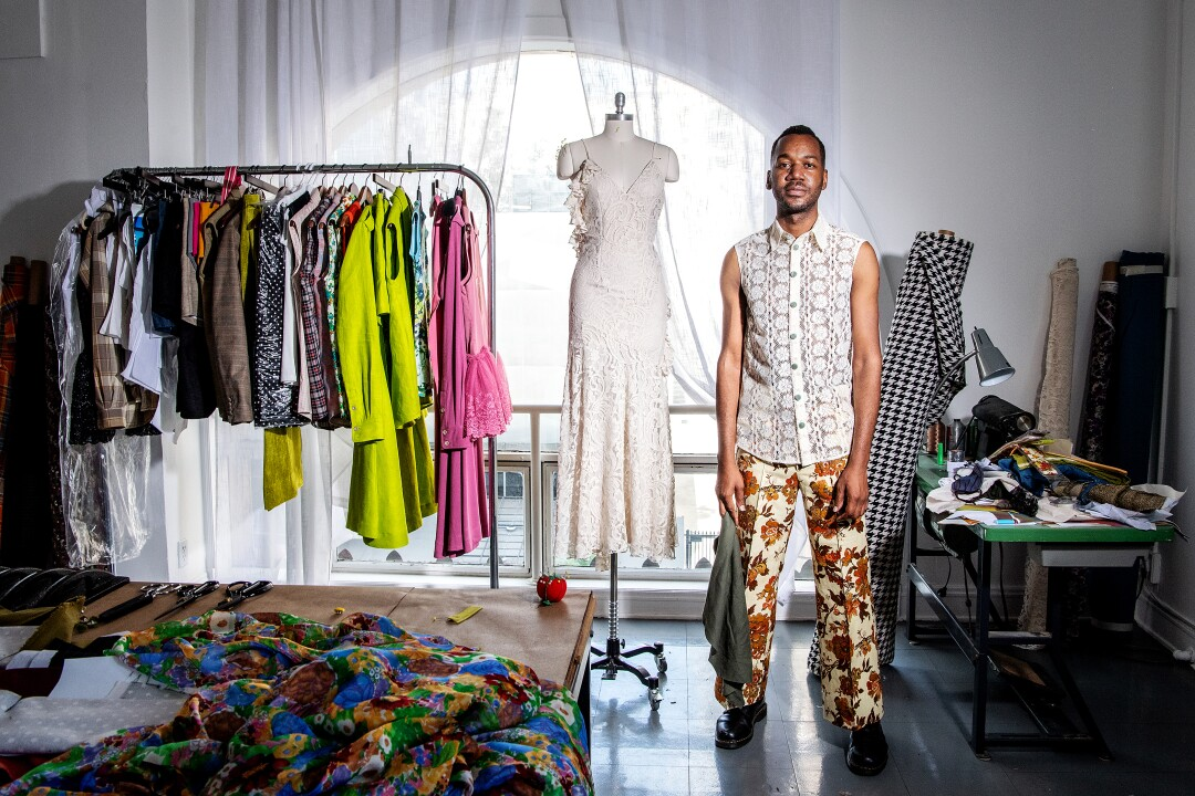 Kenneth Nicholson wearing sleeveless lace tailored shirt with floral creased trousers.