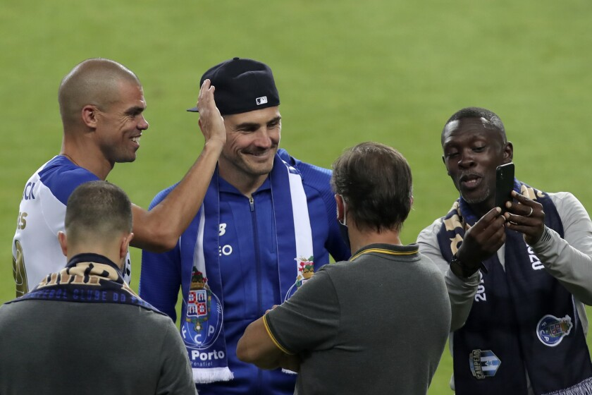 Porto former goalkeeper Iker Casillas, center with hat, joins the players celebrating on the pitch at the end of the Portuguese League soccer match between FC Porto and Sporting CP at the Dragao stadium in Porto, Portugal, Wednesday, July 15, 2020. Porto defeated Sporting 2-0 to clinch the championship with two rounds left to play. (AP Photo/Luis Vieira)