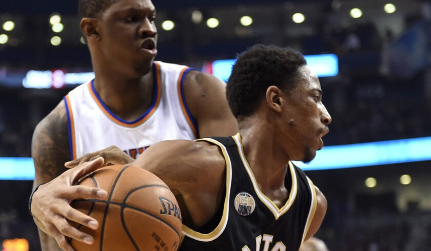 Toronto Raptors' DeMar DeRozan, right, drives past New York Knicks' Kevin Seraphin during the first half on Thursday.