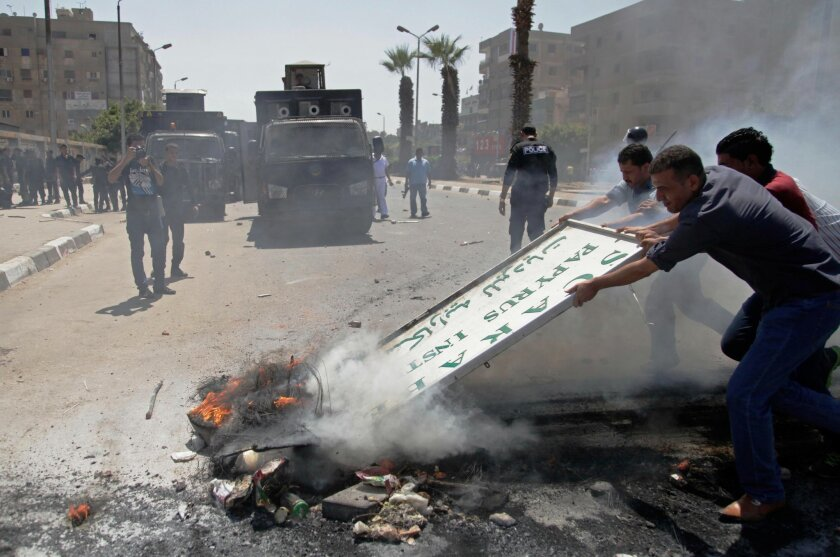Men try to clear burning debris out of a street after clashes between Egypt's security forces and supporters of ousted President Mohammed Morsi in Cairo's twin city of Giza, Egypt, Friday, July 4, 2014. A bomb accidentally exploded on a farm Friday southwest of the Egyptian capital, killing at least three suspected militants who were handling it, a security official said. (AP Photo/Ahmed Abd el-Gwad, El Shorouk newspaper) EGYPT OUT