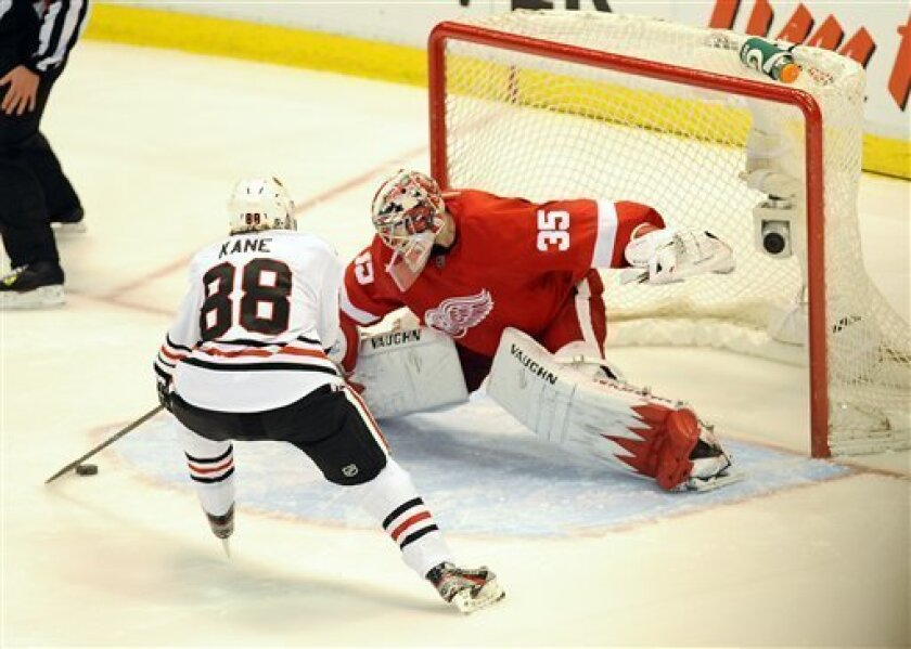 CORRECTS TO BLACKHAWKS WINNING - Chicago Blackhawks center Patrick Kane, left, gets Detroit Red Wings goalie Jimmy Howard leaning to his right before putting the puck past him for the only goal in an overtime shootout of an NHL hockey game at Joe Louis Arena in Detroit, Saturday afternoon, April 7, 2012. The Blackhawks won 3-2 in a shootout. (AP Photo/Lon Horwedel)
