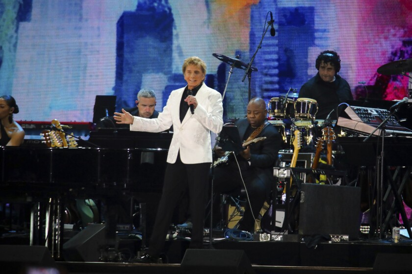 Barry Manilow performs onstage with musicians playing behind him