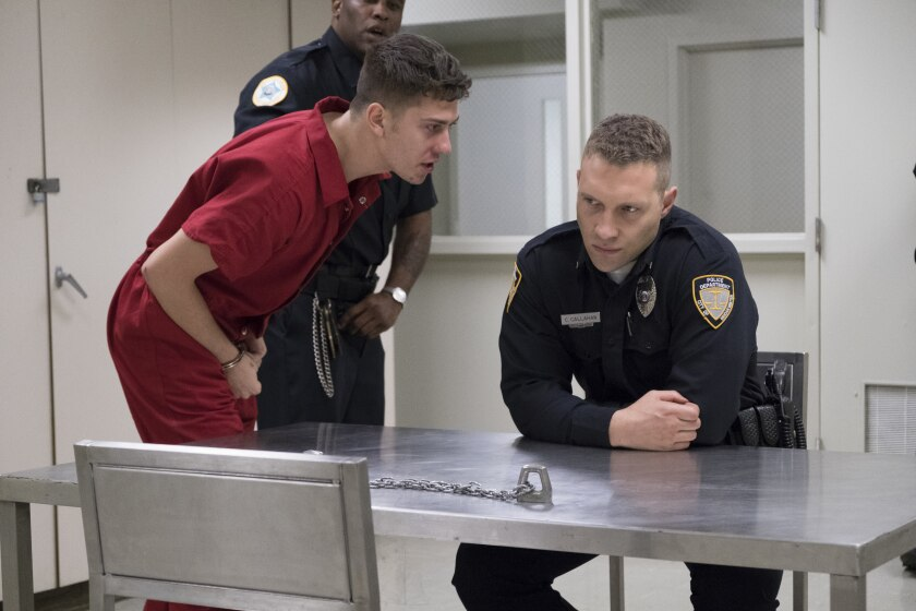 """Nat Wolff, in red jumpsuit and handcuffs, and Jai Courtney, in a police uniform, in """"Semper Fi."""""""