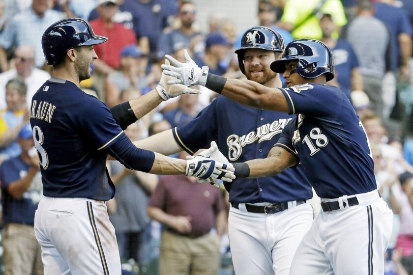 Milwaukee Brewers' Khris Davis celebrates his three-run home run with Ryan Braun (8) and Adam Lind during the third inning of a baseball game against the San Diego Padres Thursday, Aug. 6, 2015, in Milwaukee. (AP Photo/Morry Gash)