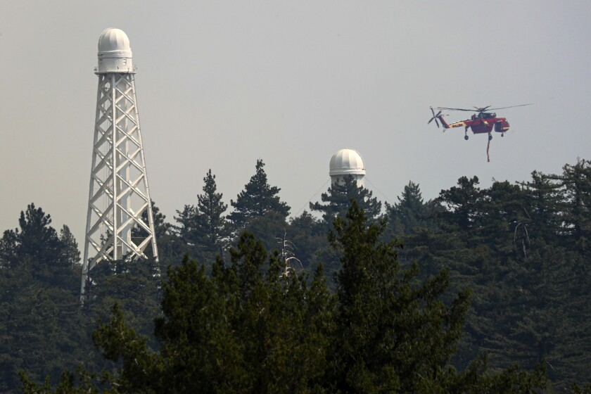 A firefighting helicopter hovers over Mt. Wilson.