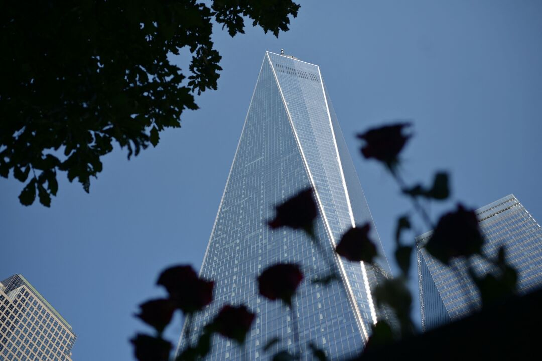 The One World Trade Center tower stands in a blue sky between other buildings.