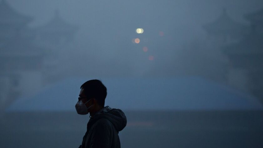 A man wears a mask to visit a Beijing park in 2016 amid heavy pollution.