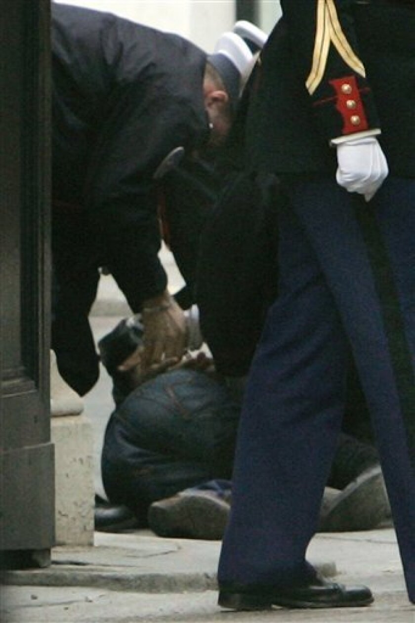 Police officers detain a man, on the ground, at the entrance of the Elysee Palace, during the visit of Montenegro's prime minister Milo Djukanovic at the Elysee Palace in Paris, Monday Dec. 15, 2008. A police official said a man carrying a knife has been arrested trying to enter the grounds of the French presidential palace. (AP Photo/Remy de la Mauviniere)