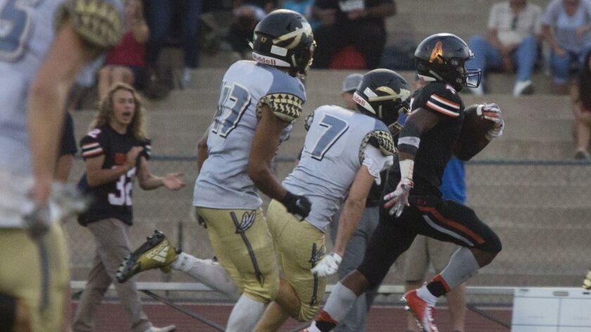 Huntington Beach's Arick McLawyer runs the ball for a touchdown against Canyon at El Modena High Sch