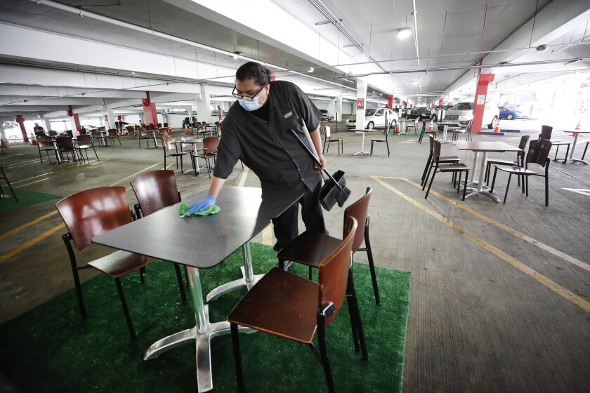 Juan Camacho wipes tables clean in an outdoor dining area created in the Glendale Galleria parking structure.