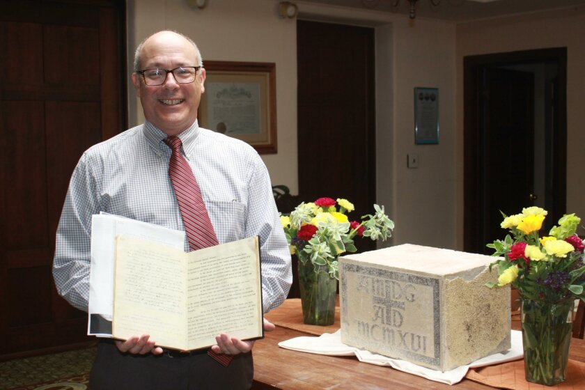 Pastor Sam Greening holds the book with the 'treasure map' that led the congregation to find the cornerstone, placed on display at right.