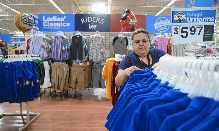 Wal-Mart plans to hire 60,000 seasonal workers, including as many as 5,000 in Southern California. Above, Wal-Mart worker Nidia Flores arranges clothing.