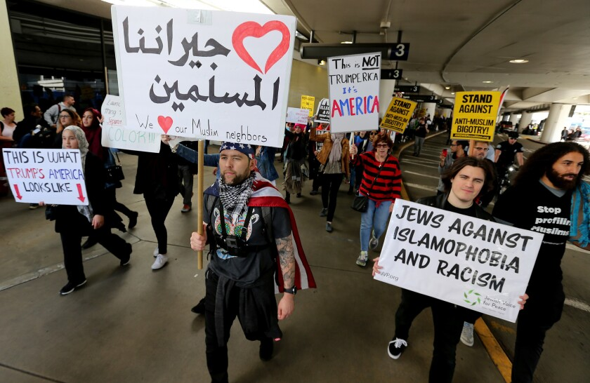 Protesters rallying against the first travel ban signed by President Trump march around Los Angeles International Airport in February.