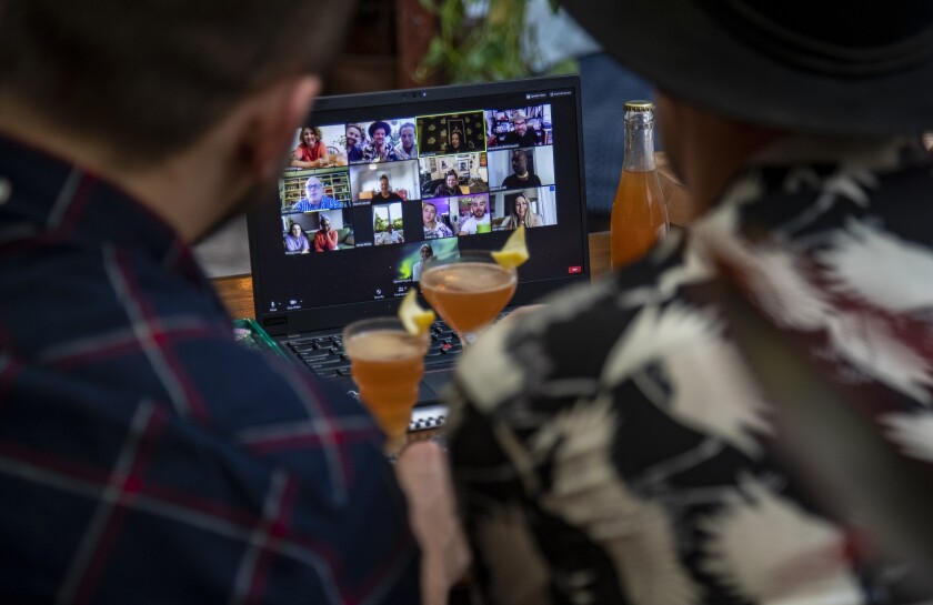 A cocktail glass in front of a computer screen.