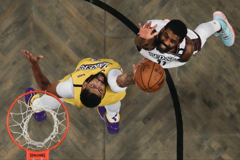 Nets guard Kyrie Irving lofts a shot over Lakers forward Anthony Davis during a game on Jan. 23, 2020, at Barclays Center in Brooklyn.