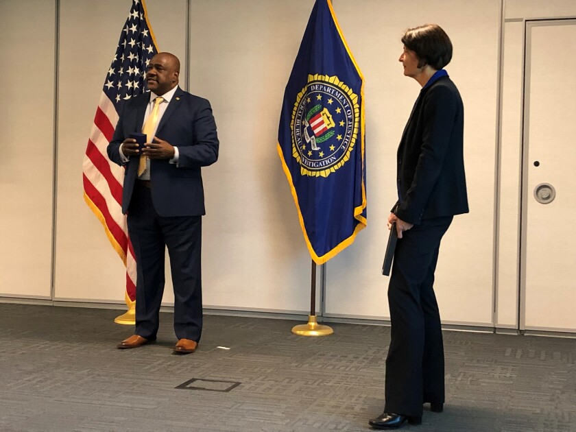 The Rev. Gerald Brown, left, accepts the FBI Director's Community Leadership Award Thursday