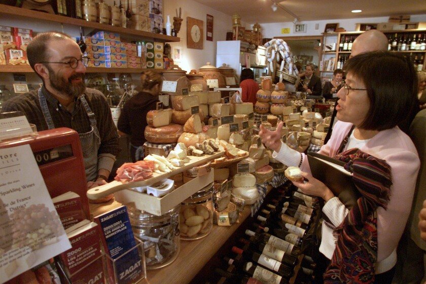Norbert Wabnig, owner of the the Cheese Store in Beverly Hills, talks cheese to customer Mamie Warrick.