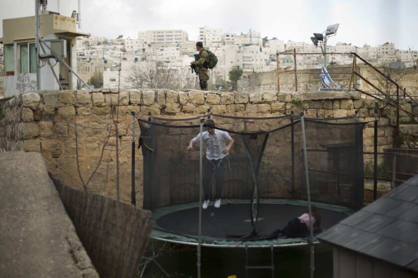 """FILE - In this March 7, 2019, file photo, settlers jump on a trampoline as an Israeli solider stands guard in the Israeli controlled part of the West Bank city of Hebron. Israel's premier human rights group has begun describing both Israel and its control of the Palestinian territories as a single """"apartheid"""" regime, using an explosive term that the Israeli government and its supporters vehemently reject. (AP Photo/Ariel Schalit, File)"""