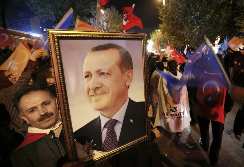 A supporter of the Justice and Development Party, (AKP), holds a portrait of Turkey's President Recep Tayyip Erdogan as people celebrate outside the AKP headquarters, in Istanbul, Turkey, late Sunday, Nov. 1, 2015. Turkey's ruling party secured a stunning victory in Sunday's snap parliamentary elec