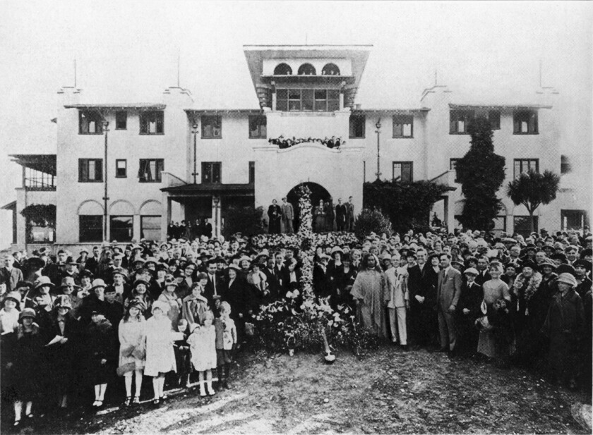 A large group of people in front of a big building
