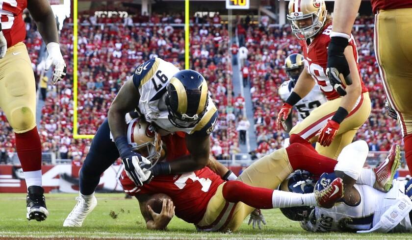 Rams defensive linemen Eugene Sims (97) and Michael Brockers (90) sack 49ers quarterback Colin Kaepernick during a game at Levi's Stadium on Nov. 2.
