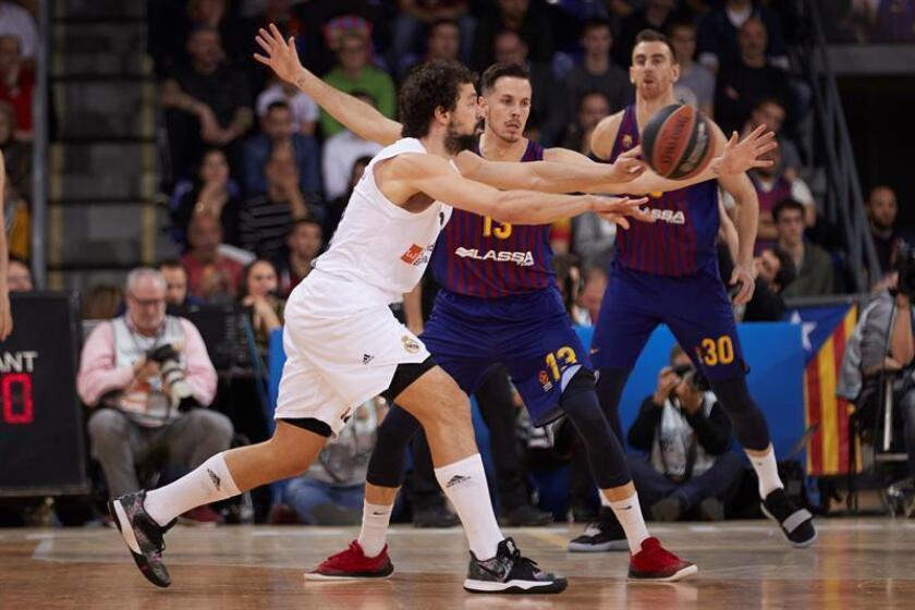 El base del Real Madrid Sergio Llull (i) intenta un pase ante el base francés del Barcelona Lassa Thomas Heurtel durante el partido de Euroliga en el Palau Blaugrana. EFE