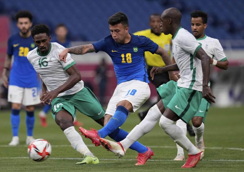 Brazil's Henrique Matheus, center, and Saudi Arabia's Abdulrahman Ghareeb, left, battle for the ball during a men's soccer match at the 2020 Summer Olympics, Wednesday, July 28, 2021, in Saitama, Japan. (AP Photo/Martin Mejia)
