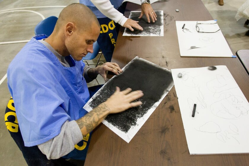"""Inside Donovan State Prison there is a new program exposing inmates to art by the name of Project Paint which teaches the basics of drawing and painting. Kyle Ruben working with a charcoal stick as part of the """"grounding"""" exercises during the class."""