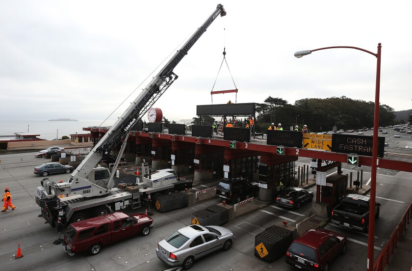 Workers use a crane to lower a new sign onto the top of the Golden Gate Bridge toll plaza. Starting Wednesday, the bridge will no longer have toll-booth operators.