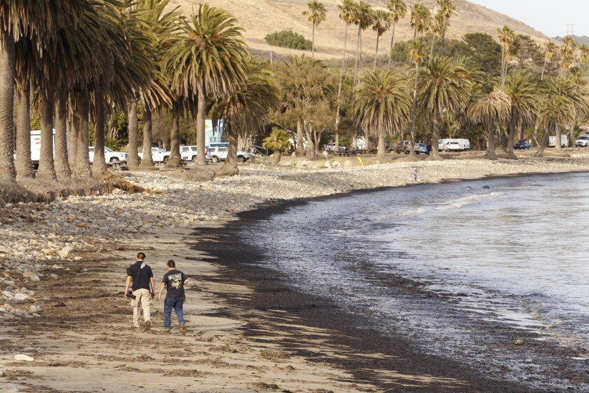 Diego Topete, left and Ryan Cullom walk May 19 on the oil-coated Refugio State Beach.
