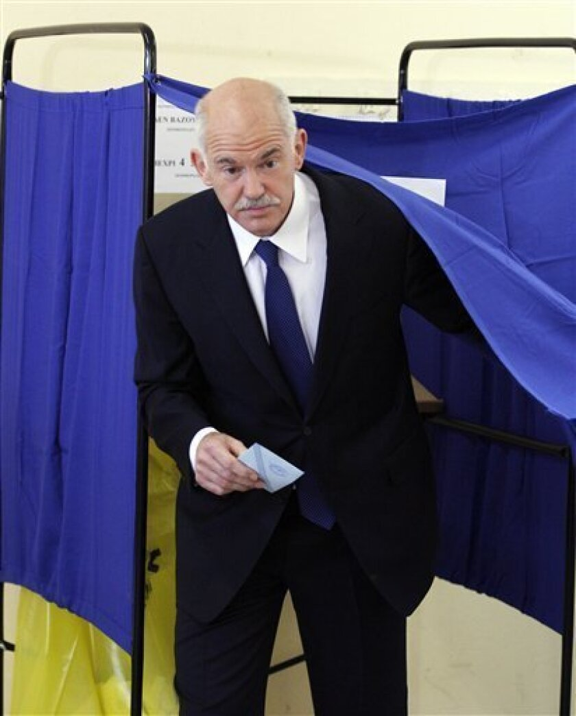Greek Prime Minister George Papandreou leaves the election booth during the municipal and regional elections in Athens, Sunday, Nov. 7, 2010. Greeks were casting ballots Sunday in local polls that could trigger a general election unless voters show support for the governing Socialists' austerity measures in the debt-strapped country. (AP Photo/Thanassis Stavrakis)