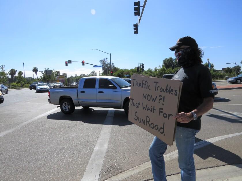 Vista resident Dr. David Clark holds a protest sign