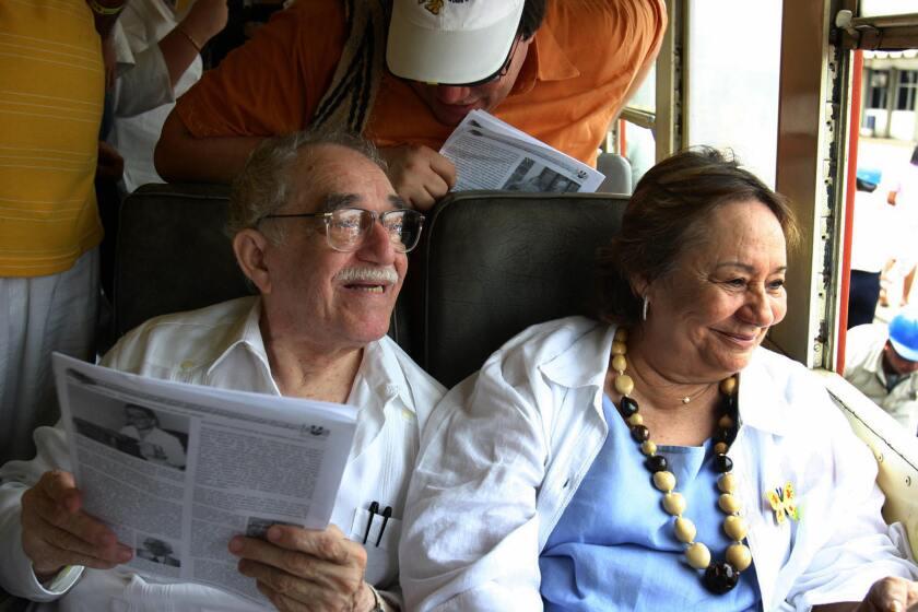Gabriel García Márquez se sienta en un vagón de tren junto a su esposa mientras ella sonríe y mira por la ventana.