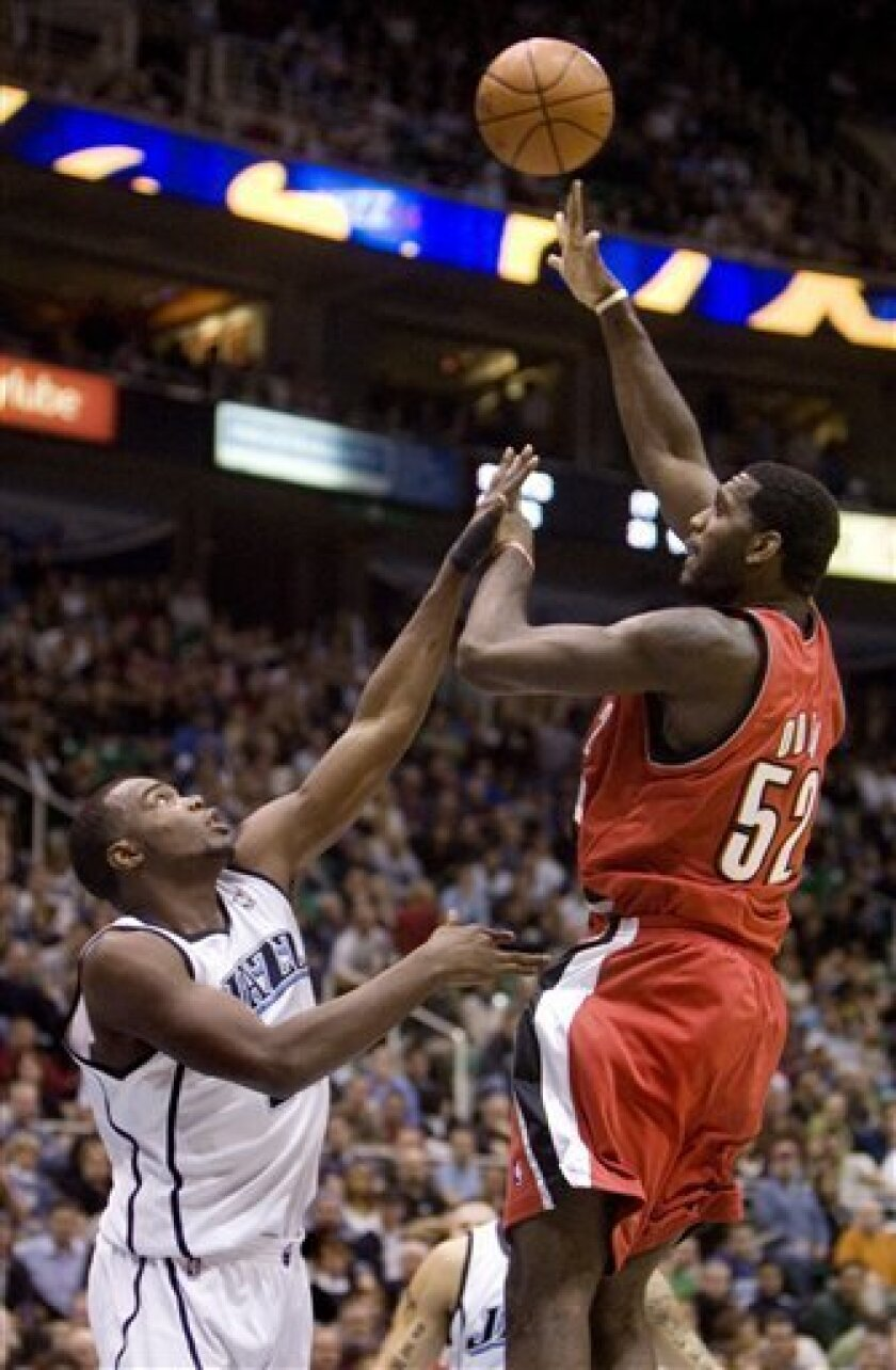 Portland Trail Blazers center Greg Oden, right, shoots over Utah Jazz forward Paul Millsap during the first quarter of the NBA basketball game Thursday, Dec. 11, 2008, in Salt Lake City. (AP Photo/Douglas C. Pizac)