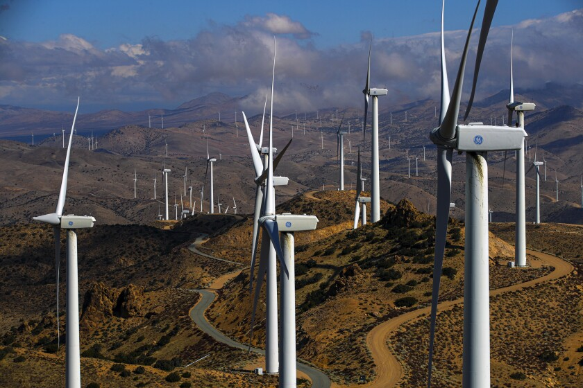 White wind turbines stand amid a mountainous landscape