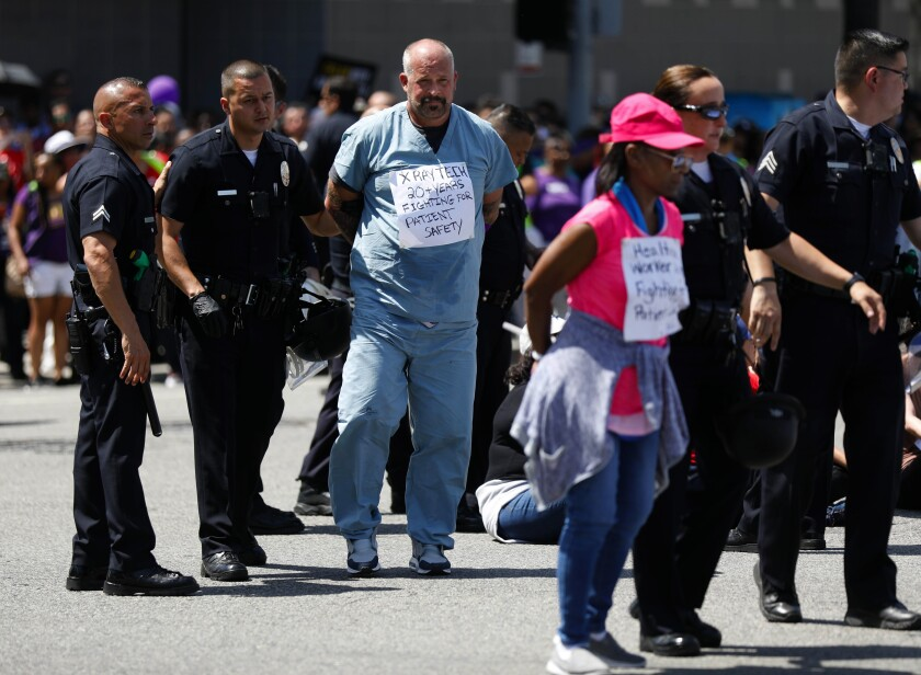Workers, clergy and politicians marched in Hollywood against the labor practices of healthcare giant Kaiser Permanente. Dozens were arrested.