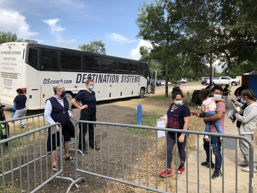 A woman watches migrants lined up to board a bus.