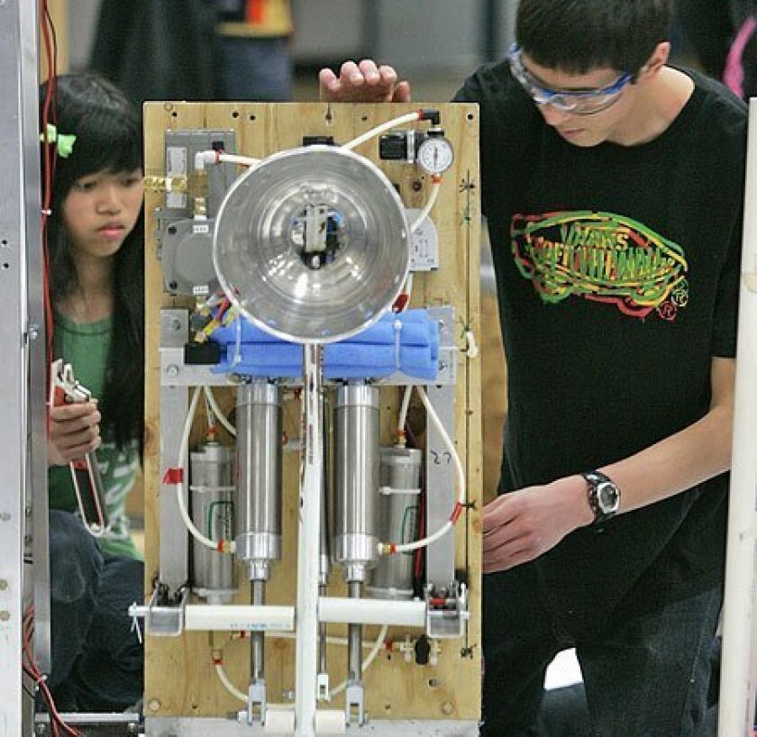 Tammy Huynh (left) and Sinjin Swartz of Preuss School's Midnight Mechanics solved a mechanical problem with their robot yesterday. (Nancee E. Lewis / Union-Tribune)